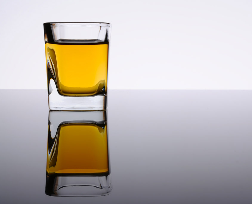 Ein Glas Whiskey spiegelt sich im Glastisch!