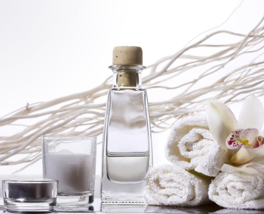 Glasflasche, Creme und Kerze weiß mit Gästehandtüchern.