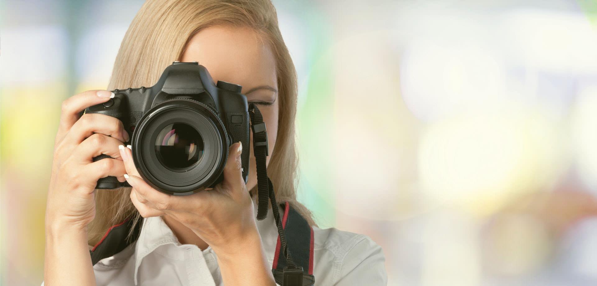 Fotografin fotografiert mit Objektiv direkt auf den Betrachter!