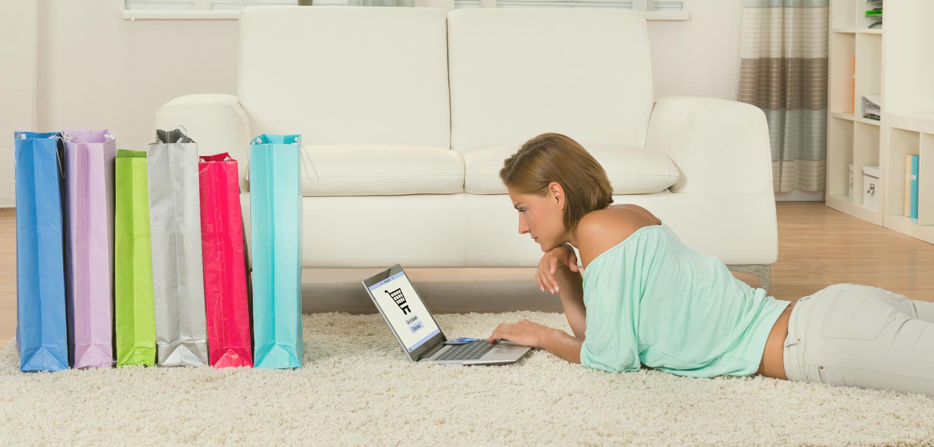 Junge Frau liegt auf dem Boden mit Ihrem Notebook und kauft online ein.