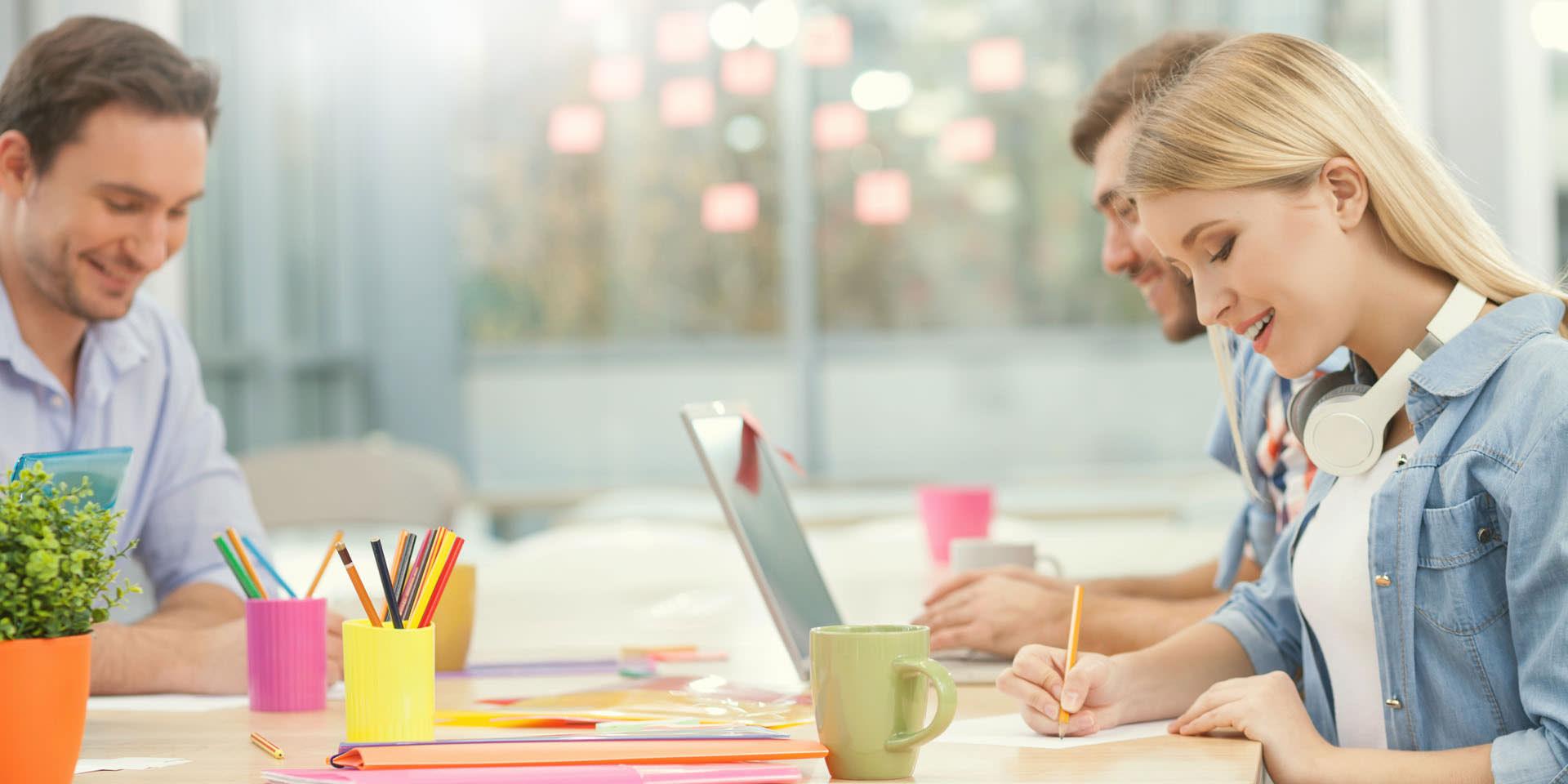 Kreatives Team entwirft Webdesign Entwürfe in einem Büro mit buntem Interieur.